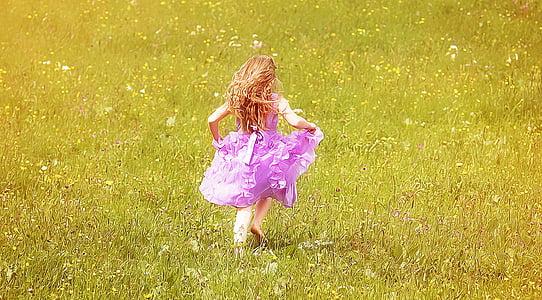 girl wearing pink dress running on grass field