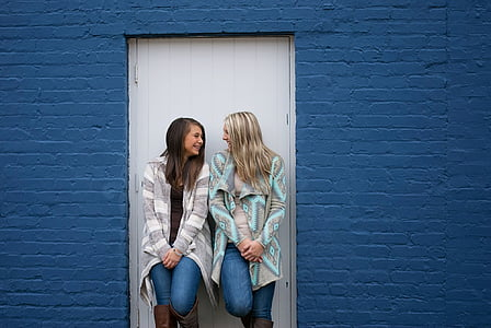 two woman standing leaning on the door
