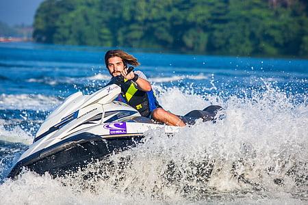 man riding watercraft near island during day