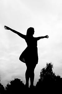 silhouette photo of woman with arms wide open