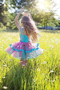 girl wearing blue and pink dress in the middle of white flower field