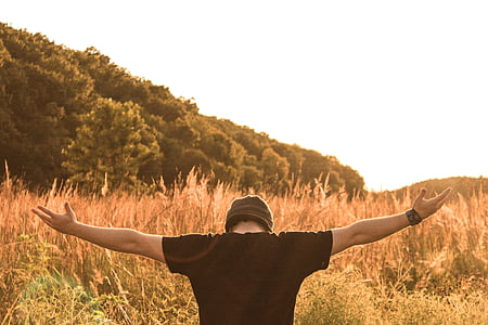 landscape photo of man arm wide open in front of grass field