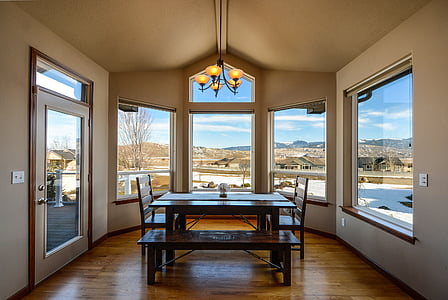 rectangular brown wooden dining table near glass windows during daytime