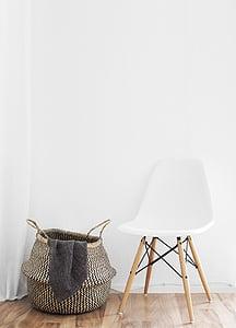 gray hamper beside white chair