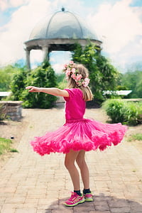 girl wearing pink tutu dress standing facing on green leaf plant selective focus photograph