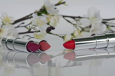 three assorted-shades of lipstick beside white petaled flowers