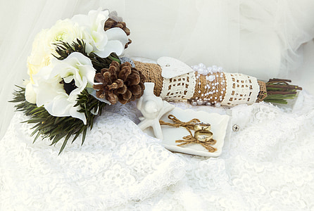 white flowers with pine cones bouquet and pair of gold-colored earrings