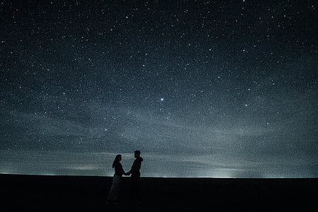 man and man holding each other's hands under starry night