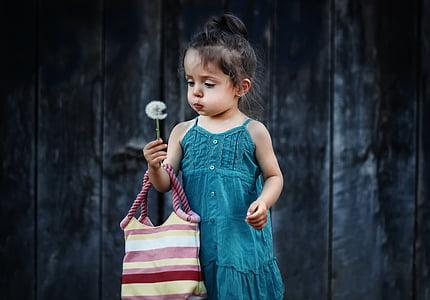 girl wearing green dress holding dandelion