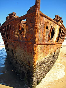 brown rusty ship docked near shore