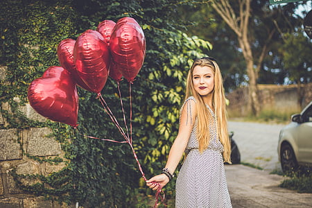 woman holding five heart red balloons