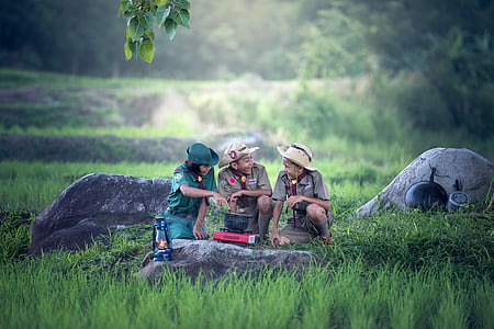 two boy scout and one girl scout cooking on pot using stove surrounded by green grass field during daytime