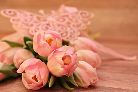 selective focus photo o fpink tulips bouquet on brown wooden surface