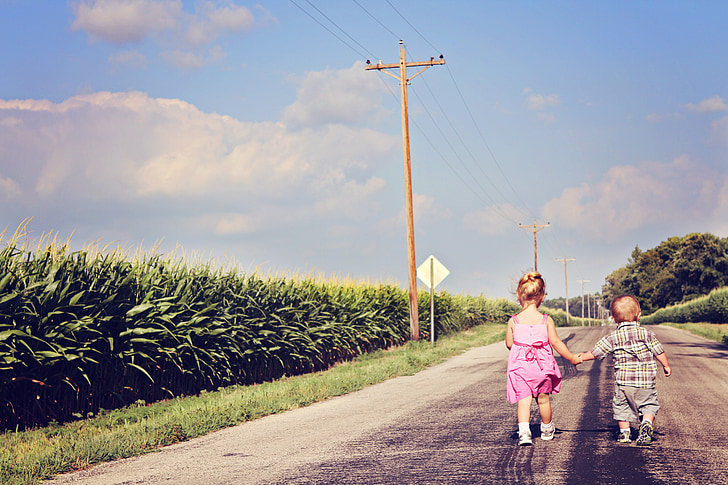 boy and girl holding hands while walking along the road
