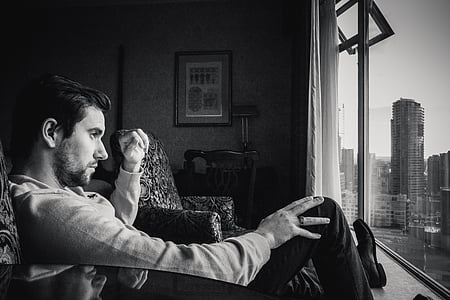 man sitting on sofa chair while staring through the window grayscale photo