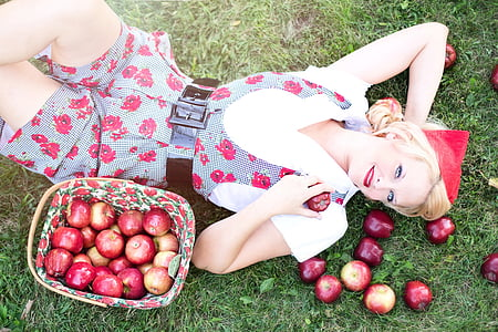 woman lying down with bunch of apples