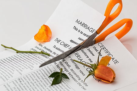 orange scissors cutting marriage certificate