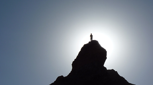 silhouette person standing on peak of mountain