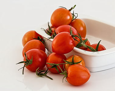 bunch of tomatoes on and white bowl