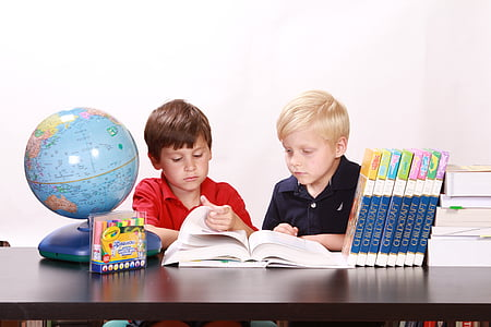 two boys sitting on chair reading book