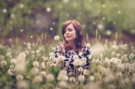 woman wearing white and black heart print top in bed of dandelion flowers selective focus photograph