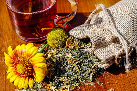yellow flower between pouch and clear glass teacup