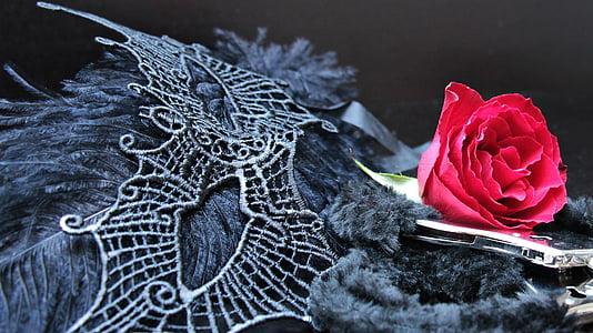 pink rose beside silver mask