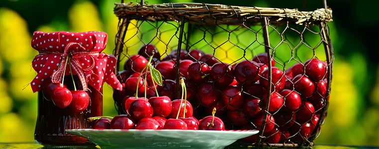photo of red cherries with basket and plate