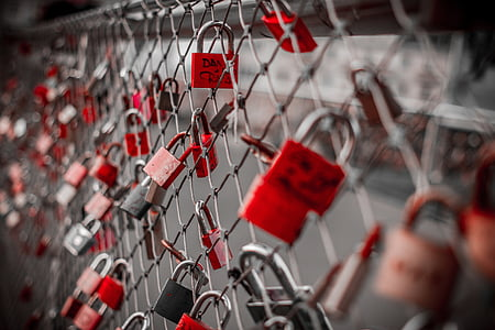 red padlocks on gray cyclone fence