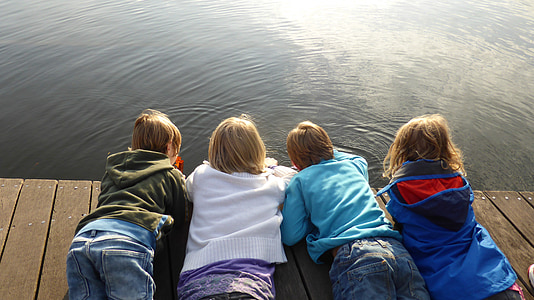 four toddlers in assorted-color jackets planking on brown wooden dock near water during daytime