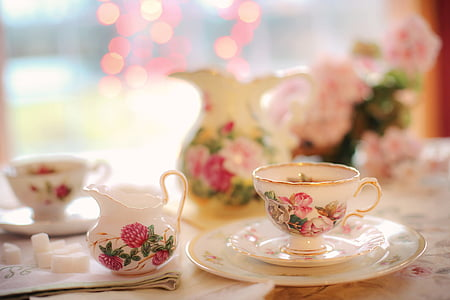 selective focus photography of white and pink floral ceramic cup and saucer
