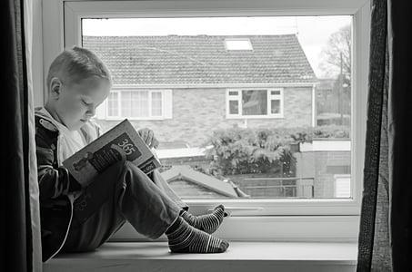 boy sitting on window reading book