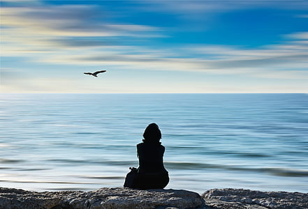 silhouette photograph of person sitting on rock near sea