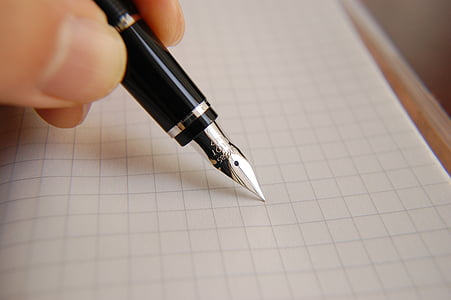 person holding black and grey fountain pen