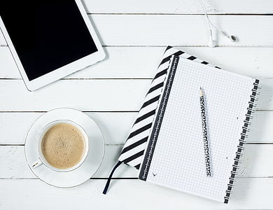 black pen on top of white notebook beside white teacup