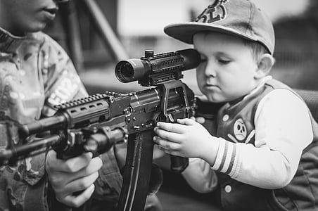 boy wearing flat brim cap holding assault rifle