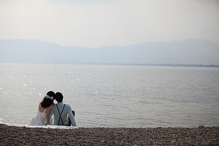 couple sitting on seashore during daytime