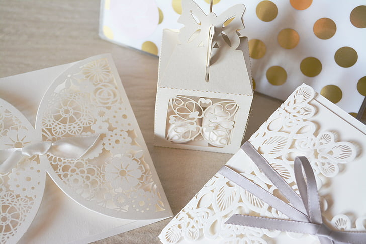 two white floral inviation cards