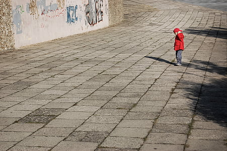 boy standing on pavement during daytime