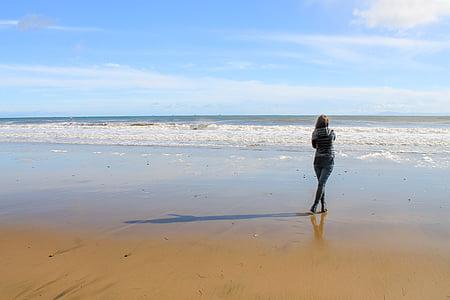 woman standing on shoreline facing back