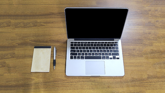 MacBook Pro, white pad, and silver click pen on top of brown wooden table