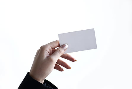 person's left hand holding white paper