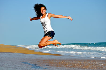 woman wearing white tank top jumping near seashore