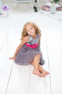 girl in gray dress sitting on white wooden floor