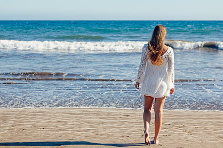 woman walking towards beach shore