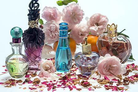 blue fragrance glass bottle beside clear fragrance bottle