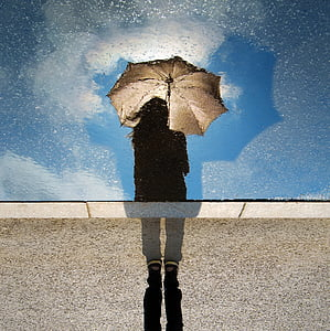 silhouette of woman with brown umbrella under bright sky