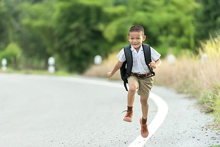 boy carrying backpack walking on road