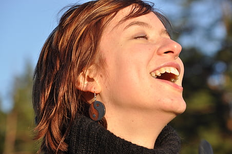 woman in black sweater laughing with eyes close