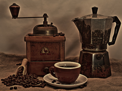brown manual coffee grinder and black and brown coffee pot behind brown and white ceramic coffee cup